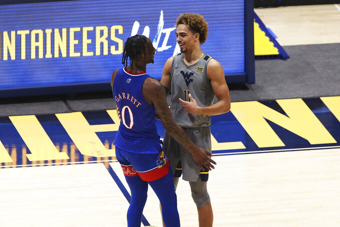 Kansas guard Marcus Garrett (0) and West Virginia forward Emmitt Matthews Jr. (11) greet each other after West Virginia wins during the second half of an NCAA college basketball game Saturday, Feb. 6, 2021, in Morgantown, W.Va. (AP Photo/Kathleen Batten)