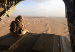 FILE - In this Sept. 17, 2015, file photo, an Emirati gunner watches for enemy fire from the rear gate of a United Arab Emirates Chinook military helicopter flying over Yemen. (AP Photo/Adam Schreck, File)