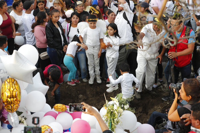 Children sing next to the grave of 7-year-old murder victim Fatima in Mexico City, Tuesday, Feb. 18, 2020. Fatima's body was found wrapped in a bag and abandoned in a rural area on Saturday. Five people have been questioned in the case, and video footage of her abduction exists. (AP Photo/Marco Ugarte)