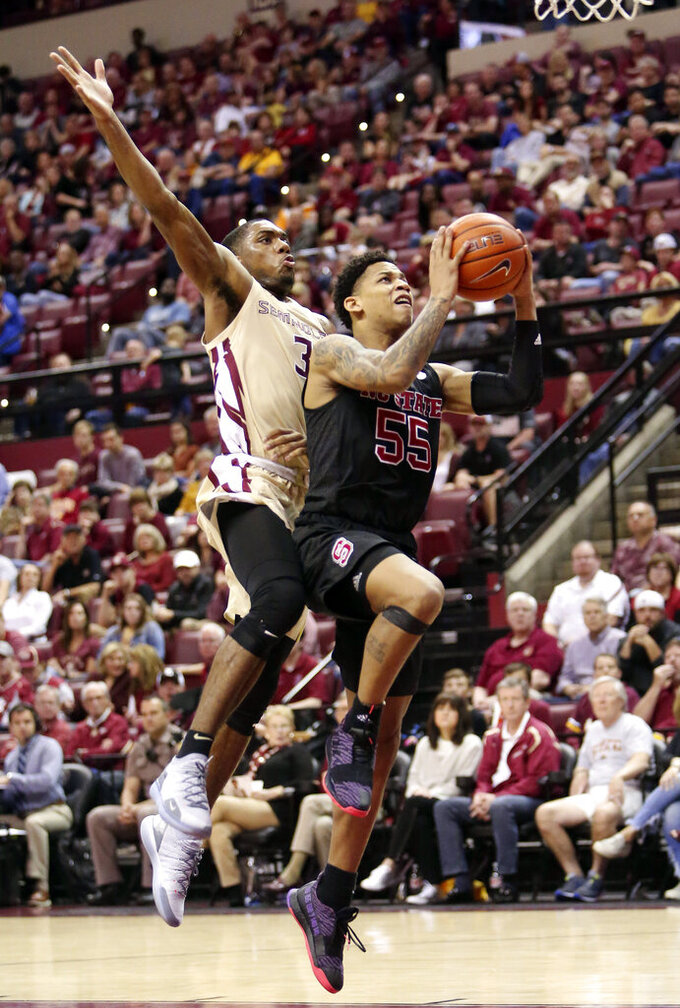 North Carolina State's Blake Harris, right, gets fouled by Florida State's Trent Forrest as he attempts a shot in the second half of an NCAA college basketball game Saturday, March 2, 2019, in Tallahassee, Fla. Florida State won 78-73. (AP Photo/Steve Cannon)