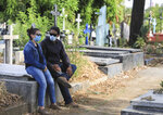 A couple wear masks as they attend a funeral at the Central cemetery of Managua, Nicaragua, Monday, May 11, 2020. President Daniel Ortega's government has stood out for its refusal to impose measures to halt the new coronavirus for more than two months since the disease was first diagnosed in Nicaragua. Now, doctors and family members of apparent victims say, the government has gone from denying the disease's presence in the country to actively trying to conceal its spread. (AP Photo/Alfredo Zuniga)