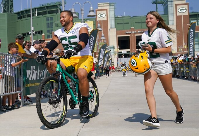 Green Bay Packers' Lane Taylor rides a bike to NFL football training camp Thursday, July 25, 2019, in Green Bay, Wis. (AP Photo/Morry Gash)
