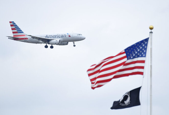 FILE- In this Sept. 21, 2018, file photo a plane flies past the American flag in Washington. American Airlines reports earnings Thursday, Oct. 25. (AP Photo/Susan Walsh, File)