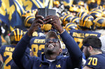 Chris Webber, a former Michigan basketball player, smiles while recording on the sidelines before an NCAA college football game against the Penn State in Ann Arbor, Mich., Saturday, Nov. 3, 2018. (AP Photo/Paul Sancya)