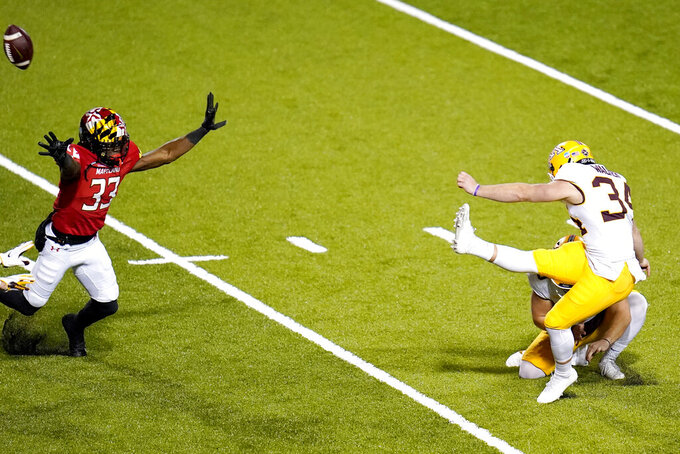 Minnesota place kicker Brock Walker, right, misses an extra point during overtime of an NCAA college football game against Maryland, Friday, Oct. 30, 2020, in College Park, Md. Maryland won 45-44 in overtime. (AP Photo/Julio Cortez)