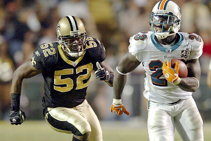 FILE - In this Sunday, Oct. 30, 2005 file photo, running back Ronnie Brown (23) runs against New Orleans Saints linebacker Sedrick Hodge (52) gives chase during the fourth quarter, in Baton Rouge, La. Federal prosecutors said Wednesday, Sept. 11, 2019, that former New Orleans Saint Hodge sold oxycodone pills in Cartersville, Georgia, just northwest of Atlanta. The 40-year-old Hodge is accused of illegal distribution of controlled substances, among other charges.(AP Photo/Bill Feig, File)