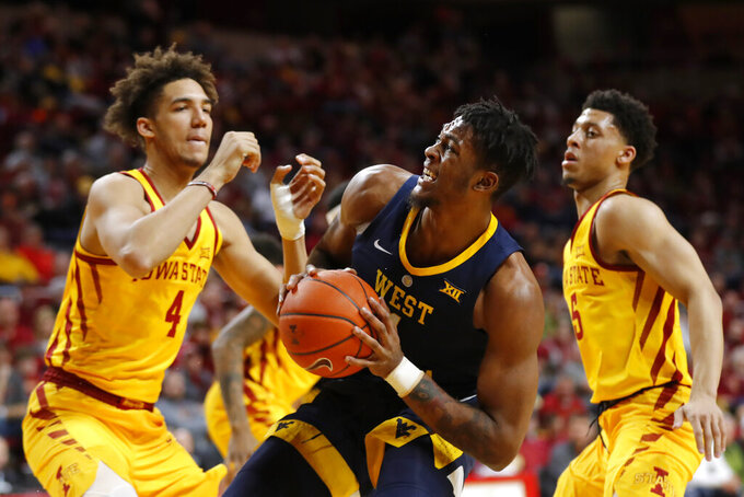 West Virginia forward Derek Culver, center, drives to the basket between Iowa State defenders George Conditt IV, left, and Lindell Wigginton, right, during the first half of an NCAA college basketball game Wednesday, Jan. 30, 2019, in Ames, Iowa. (AP Photo/Charlie Neibergall)