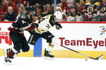 Boston Bruins' Jake BeBrusk (74) runs down the puck against the Arizona Coyotes' Jordan Oesterle (82) during the first period of an NHL hockey game Saturday, Oct. 5, 2019, in Glendale, Ariz. (AP Photo/Darryl Webb)