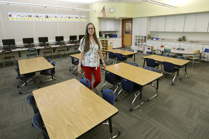 First-grade teacher Hillary Madrigal is photographed in her classroom Thursday, Aug. 22, 2019, in Salt Lake City. Across the country, teachers and school districts alike are grappling with the latest political and economic realities of educator pay. Madrigal jumped to the nearby school district last year, lured by higher salaries that would allow her to quit her second job as a housekeeper and buy a new car.