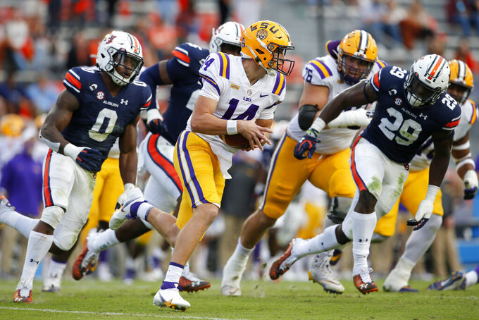 LSU quarterback Max Johnson (14) scrambles away form Auburn pressure during the second half of an NCAA college football game on Saturday, Oct. 31, 2020, in Auburn, Ala. (AP Photo/Butch Dill)
