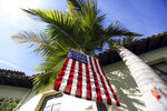 FILE - This March 7, 2017 file photo shows a U.S. flag hanging from a palm tree outside a polling place at the Bel-Air Bay Club in the Pacific Palisades area of Los Angeles. With the 2020 elections approaching, the latest California voter registration figures tell a familiar story: Democrats are expanding their ranks, Republicans are struggling and the fastest-growing group remains those voters aligned with no party at all - independents. The figures released Wednesday, Nov. 6, 2019 by Secretary of State Alex Padilla also show that more than 80 percent of eligible residents are registered to vote, the highest percentage since 1952. (AP Photo/Reed Saxon, File)