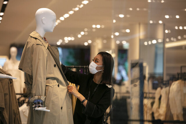 FILE - In this March 1, 2020, file photo, a department store employee with a mask dresses a mannequin in Tokyo. Japan's economy shrank at annual rate of 27.8% in April-June, the worst contraction on record, as the coronavirus pandemic slammed consumption and trade, government data released Monday, Aug. 17, 2020, show.  (AP Photo/Jae C. Hong, File)
