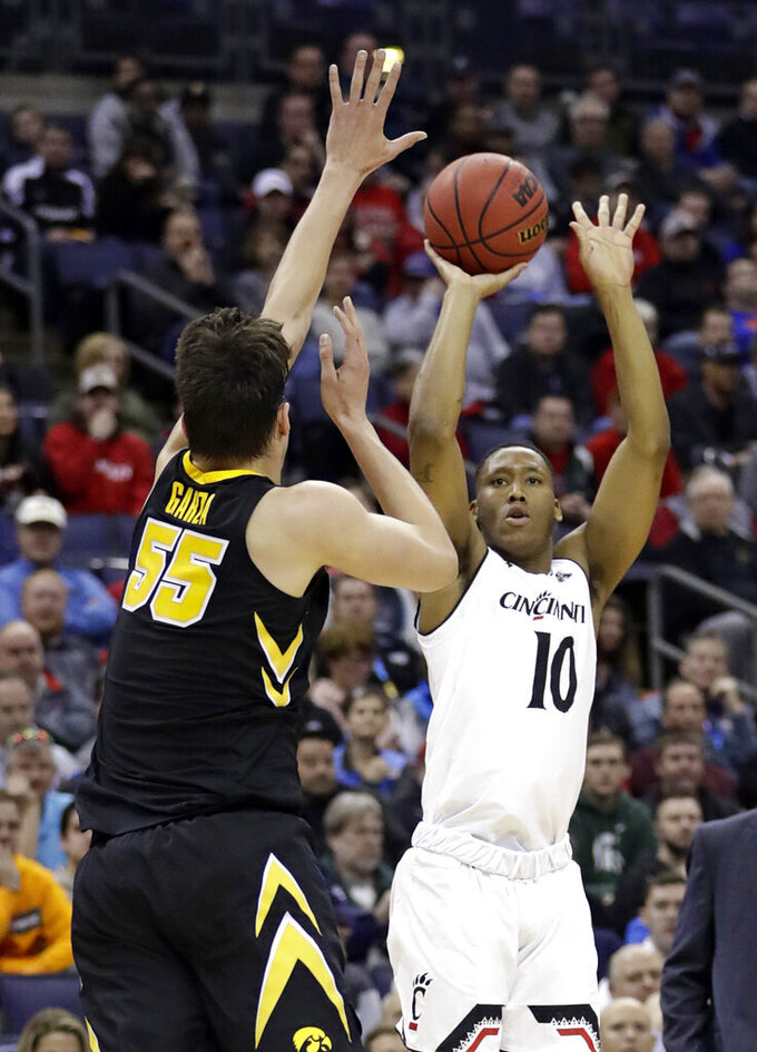 Cincinnati's Rashawn Fredericks (10) shoots over Iowa's Luka Garza (55) in the first half during a first round men's college basketball game in the NCAA Tournament in Columbus, Ohio, Friday, March 22, 2019. (AP Photo/Tony Dejak)