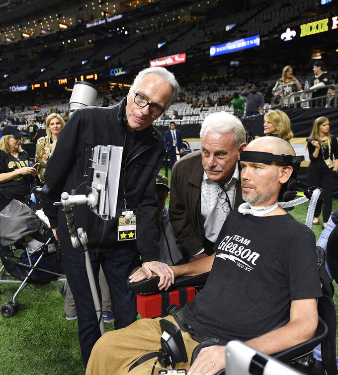 FILE - In this Jan. 13, 2019, file photo, former New Orleans Saints player Steve Gleason, who suffers from amyotrophic lateral sclerosis (ALS), looks at his screen with former Saints assistant coach Joe Vitt, center, before an NFL divisional playoff football game against the Philadelphia Eagles, in New Orleans. He's the Saints' biggest fan and the perfect symbol of a city that knows a thing or two about overcoming hardship. As the Big Easy goes for another championship, Gleason is along for the ride. Even though his body failed him, perhaps because of the game he loved so much, he never lost the will to live and love and make a difference. (AP Photo/Bill Feig, File)
