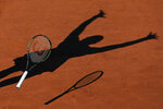FILE - In this June 6, 2015, file photo, Serena Williams casts a shadow on the clay as she drops her racket while celebrating winning the final of the French Open tennis tournament against Lucie Safarova of the Czech Republic in three sets, 6-3, 6-7, 6-2, at Roland Garros stadium in Paris. (AP Photo/David Vincent, File)