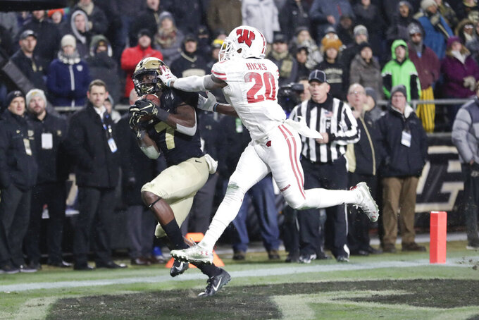 FILE - In this Nov. 17, 2018, file photo, Purdue wide receiver Isaac Zico (7) makes a catch for a touchdown in front of Wisconsin cornerback Faion Hicks (20) during overtime in an NCAA college football game in West Lafayette, Ind. Wisconsin returns every cornerback and still has no seniors at the position. Coach Paul Chryst said he expects sophomore Hicks to take a huge leap after 35 tackles and an interception in 12 games (11 starts) last season. (AP Photo/Michael Conroy, File)