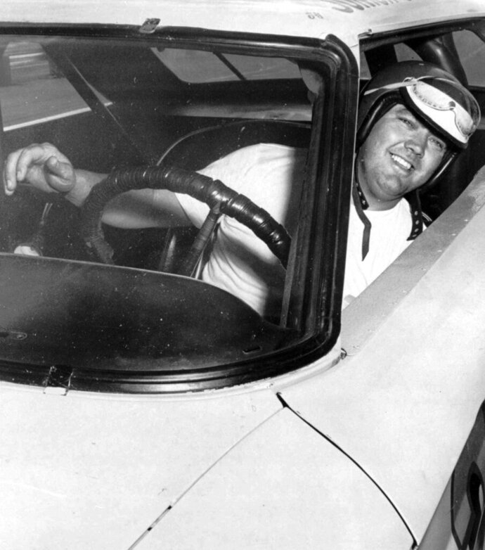 FILE - In this June 3, 1964, file photo, Junior Johnson peers from his car after winning the pole position for the Dixie 400 stock car race at Atlanta International Raceway in Atlanta. Johnson, who won 50 NASCAR Cup Series races as a driver and 132 as an owner and was part of the inaugural class inducted into the NASCAR Hall of Fame in 2010, has died at 88. (AP Photo/File)