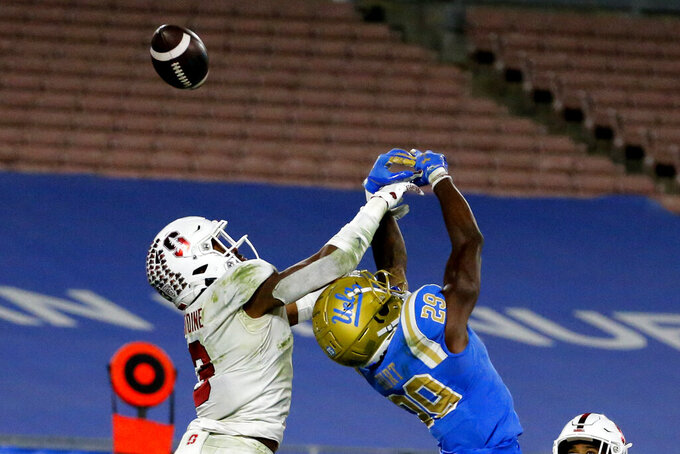 UCLA wide receiver Delon Hurt (29) misses a catch next to Stanford free safety Malik Antoine (3) during  overtime of an NCAA college football game Saturday, Dec. 19, 2020, in Pasadena, Calif.  Stanford won 48-47 in overtime. (AP Photo/Ringo H.W. Chiu)