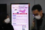 FILE - In this Monday, Jan. 27, 2020, file photo, a poster warning about coronavirus is seen as passengers wear masks in a departure lobby at Incheon International Airport in Incheon, South Korea. British Airways and Asian budget carriers Lion Air and Seoul Air are suspending all flights to China as fears spread about the outbreak of a new virus that has killed more than 130 people. British Airways said Wednesday it is immediately suspending all flights to and from mainland China after the U.K. government warned against unnecessary travel to the country. (AP Photo/Ahn Young-joon, File)