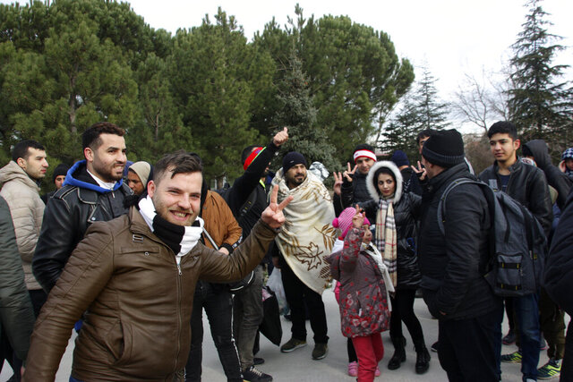 Migrants react as they walk to the border gate of Pazarkule in Edirne, near Turkey-Greece border, early Friday, Feb. 28, 2020. An air strike by Syrian government forces killed scores of Turkish soldiers in northeast Syria, a Turkish official said Friday, marking the largest death toll for Turkey in a single day since it first intervened in Syria in 2016. (AP Photo/Ergin Yildiz)