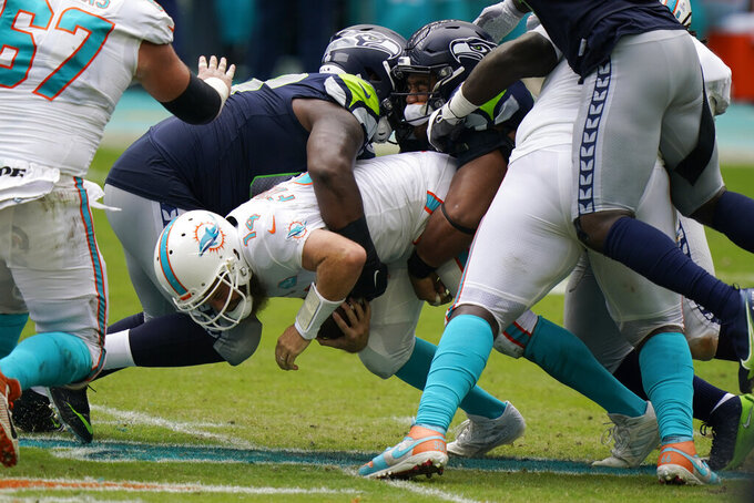 Miami Dolphins quarterback Ryan Fitzpatrick (14) is sacked by Seattle Seahawks defensive tackles Anthony Rush and Bryan Mone, during the first half of an NFL football game, Sunday, Oct. 4, 2020 in Miami Gardens, Fla. (AP Photo/Wilfredo Lee)