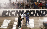 Martin Truex Jr. holds the checkered flag after winning the NASCAR Cup Series auto race at Richmond Raceway in Richmond, Va., Saturday, April 13, 2019. (AP Photo/Steve Helber)