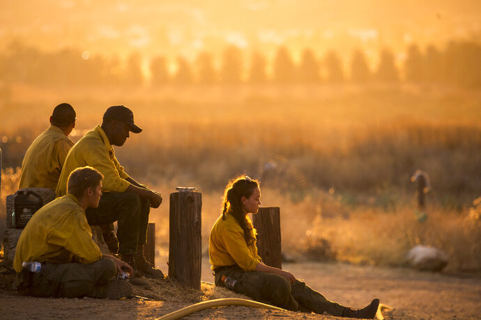 Firefighters rest during a wildfire in Yucaipa, Calif., Saturday, Sept. 5, 2020. Firefighters trying to contain the massive wildfires in Oregon, California and Washington state are constantly on the verge of exhaustion as they try to save suburban houses, including some in their own neighborhoods. (AP Photo/Ringo H.W. Chiu)