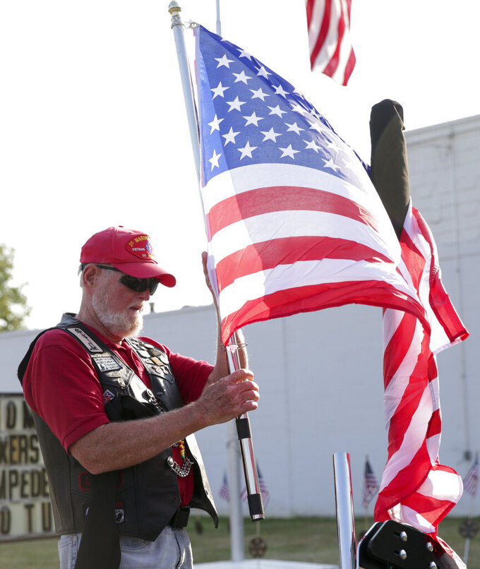 Jim Jamison of Westfield, Ind. unfurls a flag to place at the back of his motorcycle before the funeral procession for Marine Cpl. Humberto Sanchez, Tuesday, Sept. 14, 2021 in Logansport, Ind. Sanchez was one of 13 U.S. service members to die in an explosion during evacuation efforts in Afghanistan. (Nikos Frazier/Journal & Courier via AP)