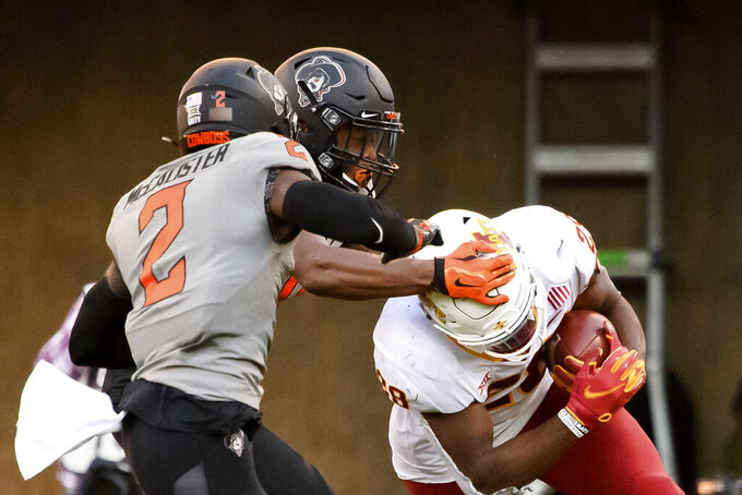 Oklahoma State safety Tanner McCalister, left, and Oklahoma State cornerback Christian Holmes, center, reaches for the head of Iowa State running back Breece Hall (28) during the second half of an NCAA college football game Saturday, Oct. 24, 2020, in Stillwater, Okla. AP Photo/Brody Schmidt)
