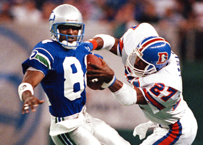 FILE - In this Oct. 23, 1989, file photo, Seattle Seahawks' Louis Clark (84) brings in a pass as Denver Broncos' Steve Atwater defends during an NFL football game in Seattle. In the last decade, four defensive backs from the modern era have made the Pro Football Hall of Fame. John Lynch, now the general manager of the 49ers who will play the Chiefs in Sunday's Super Bowl, is up for the seventh time. Steve Atwater is a finalist for the third time. LeRoy Butler and first-year eligible Troy Polamalu complete the quartet of safeties among the 15 final candidates for the Pro Football Hall of Fame. (AP Photo/Barry Sweet, File)