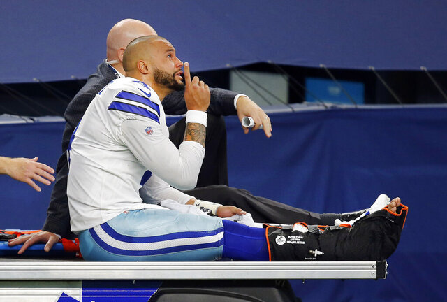 Dallas Cowboys quarterback Dak Prescott (4) points skyward as he is carted off the field after sustaining a leg injury in the third quarter of an NFL football game against the New York Giants in Arlington, Texas, Sunday, Oct. 11, 2020. (Tom Fox/The Dallas Morning News via AP)