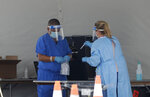 Healthcare workers put a vial containing a test swab into a bag after testing a driver at a drive-through coronavirus testing site outside of Hard Rock Stadium, Friday, June 26, 2020, in Miami Gardens, Fla. Florida banned alcohol consumption at its bars Friday as its daily confirmed coronavirus cases neared 9,000, a new record that is almost double the previous mark set just two days ago. (AP Photo/Wilfredo Lee)