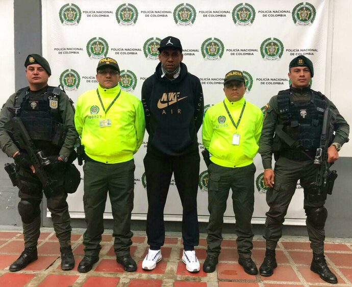 In this handout photo released by Colombia's National Police, former Southampton and Portsmouth soccer player Jhon Viafara stands flanked by police officers after his arrest on a U.S. drug warrant, in Jamundi, Colombia, Tuesday, March 19, 2019. Colombia's chief prosecutor's office said that prosecutors in Texas believe the midfielder was part of a criminal network tied to the nation's Gulf drug cartel, which for a decade moved large shipments of cocaine into the U.S. (Colombia's National Police via AP)