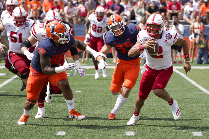Nebraska quarterback Adrian Martinez, right, scrambles under pressure from Illinois defensive lineman Keith Randolph Jr. (88) and Jake Hansen during the first half of an NCAA college football game Saturday, Aug. 28, 2021, in Champaign , Ill. (AP Photo/Charles Rex Arbogast)