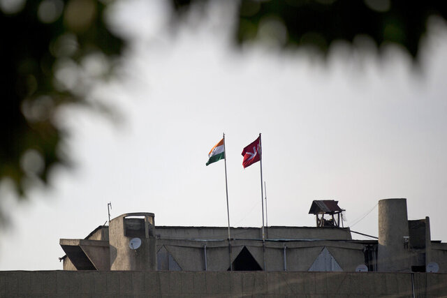 FILE - In this Aug. 9, 2019, file photo, an Indian national flag, left, is hoisted next to a Jammu and Kashmir state flag on the government secretariat building after New Delhi scrapped the disputed region's semi-autonomy in Srinagar, Indian controlled Kashmir. Indian-controlled Kashmir has remained on edge after New Delhi last summer scrapped the disputed region's semi-autonomy amid a near-total clampdown. While deeply unpopular in Muslim-majority Kashmir, the sudden move resonated in India, where Prime Minister Narendra Modi was cheered by supporters for fulfilling a long-held Hindu nationalist pledge.  (AP Photo/Dar Yasin, File)