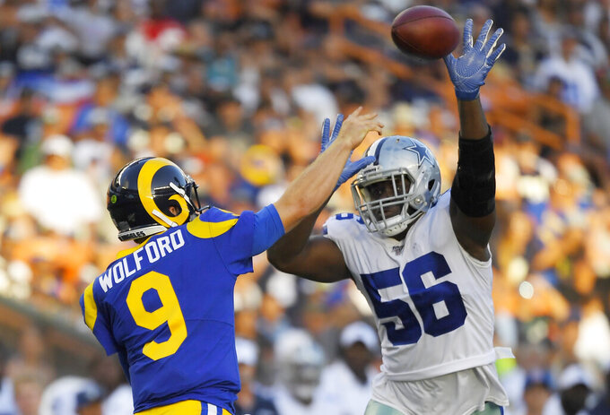 Dallas Cowboys defensive end Joe Jackson, right, tries to block the pass of Los Angeles Rams quarterback John Wolford during the second half of a preseason NFL football game Saturday, Aug. 17, 2019, in Honolulu. (AP Photo/Mark J. Terrill)