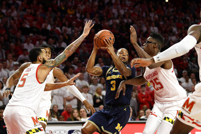 Michigan guard Zavier Simpson (3) looks to pass against Maryland forward Jalen Smith (25) and guard Eric Ayala (5) during the first half of an NCAA college basketball game, Sunday, March 8, 2020, in College Park, Md. (AP Photo/Nick Wass)