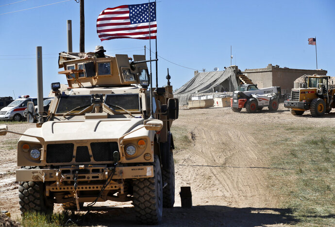 FILE - In this Wednesday, April 4, 2018 file photo, a U.S. soldier, left, sits on an armored vehicle behind a sand barrier at a newly installed position near the front line between the U.S-backed Syrian Manbij Military Council and the Turkish-backed fighters, in Manbij, north Syria. The U.S. military said Friday it has started pulling equipment, but not troops, out of Syria as a first step in meeting President Donald Trump's demand for a complete military withdrawal. (AP Photo/Hussein Malla, File)