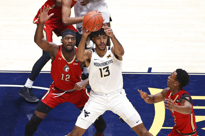 West Virginia forward Isaiah Cottrell (13) is defended by Northeastern forward Alex Nwagha (12) and guard Tyson Walker (2) during the first half of an NCAA college basketball game Tuesday, Dec. 29, 2020, in Morgantown, W.Va. (AP Photo/Kathleen Batten)