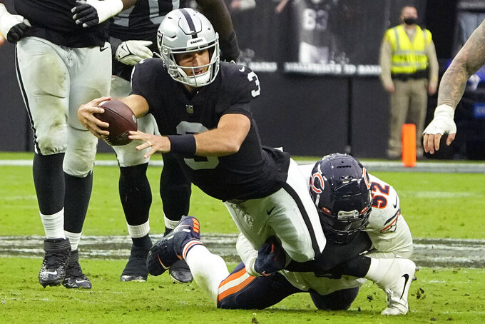 Las Vegas Raiders quarterback Nathan Peterman (3) is tackled by Chicago Bears outside linebacker Khalil Mack (52) during the second half of an NFL football game, Sunday, Oct. 10, 2021, in Las Vegas. (AP Photo/Rick Scuteri)