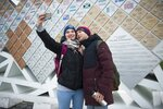 In this photo taken on Friday, Jan. 12, 2018, two visitors take a selfie in front of a board in the Olympic Park in Sochi displaying the names of 2014 Winter Olympic medalists, Russia. The Russian government spent an estimated $51 billion on the Olympics and related infrastructure for Sochi, and the city's seeing the benefits. (AP Photo/Artur Lebedev)