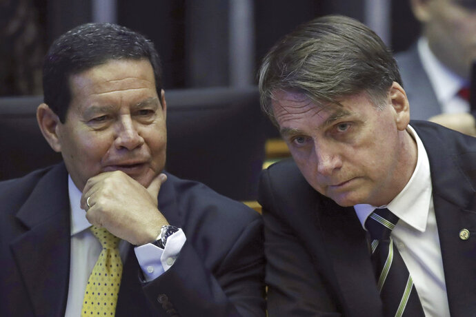 FILE - In this Nov. 6, 2018 file photo, Brazilian President-elect Jair Bolsonaro, right, and his Vice President Gen. Hamilton Mourao attend a ceremony marking the 30th anniversary of Brazil's constitution at Congress in Brasilia, Brazil. Mourao, a retired general, has made several polemical statements, such as defending torture during Brazil's dictatorship. (AP Photo/Eraldo Peres, File)
