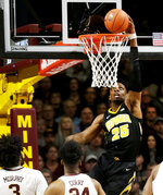 Iowa forward Tyler Cook (25) dunks in front of Minnesota forwards Jordan Murphy (3) and Eric Curry (24) during the first half of an NCAA college basketball game Sunday, Jan. 27, 2019, in Minneapolis. (AP Photo/Andy Clayton-King)