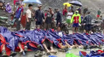 In this image made from video, people gather near the bodies of victims of a landslide near a jade mining area in Hpakant, Kachin state, northern Myanmar Thursday, July 2, 2020. Myanmar government says a landslide at a jade mine has killed dozens of people.  (AP Photo/Zaw Moe Htet)