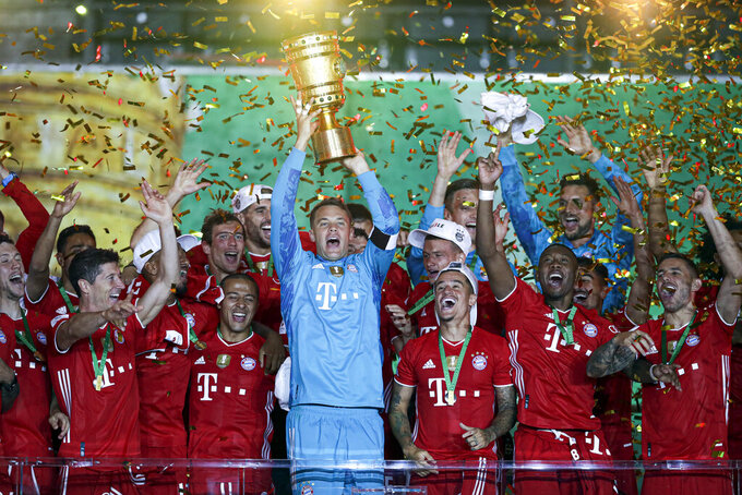 FILE - In this Saturday, July 4, 2020 file photo, Bayern Munich players celebrate after winning the trophy in the German soccer cup (DFB Pokal) final match between Bayer 04 Leverkusen and FC Bayern Munich in Berlin, Germany. German soccer club Union Furstenwalde could have had the game of a lifetime. The small club was due to host Bundesliga team Wolfsburg in the first round of the German Cup but the coronavirus pandemic meant that wasn't possible. (AP Photo/Michael Sohn, File)