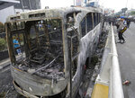 Indonesian police check burnt buses in Jakarta, Indonesia, Wednesday, May 22, 2019. Supporters of the losing presidential candidate burned vehicles and battled police and the government announced restrictions on social media. (AP Photo/Achmad Ibrahim)