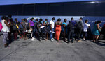 Migrants, many from Haiti, board a bus after they were processed and released after spending time at a makeshift camp near the International Bridge, Monday, Sept. 20, 2021, in Del Rio, Texas. The U.S. is flying Haitians camped at Texas border town back to their homeland and trying to block others from crossing the border from Mexico. (AP Photo/Eric Gay)