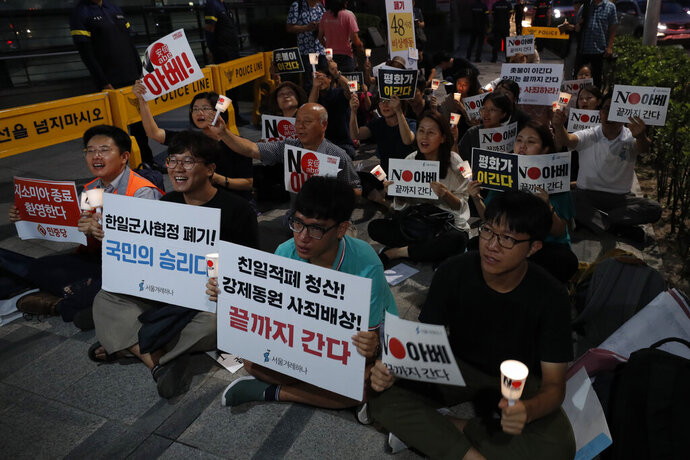 South Korean protesters react during a rally about the General Security of Military Information Agreement, or GSOMIA, in front of Japanese embassy in Seoul, South Korea, Thursday, Aug. 22, 2019. South Korea said Thursday it will terminate an intelligence-sharing deal with Japan that focused on classified information about North Korea, a surprise announcement that is likely to set back U.S. efforts to bolster security cooperation with two of its most important allies in the Asian region. The sign read