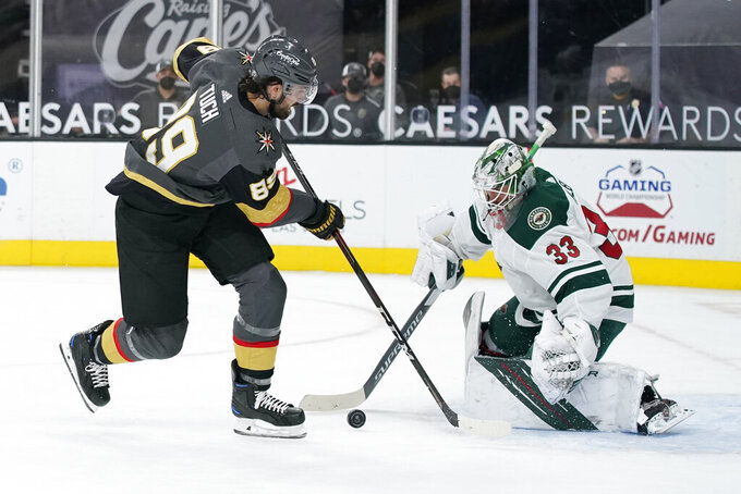 Minnesota Wild goaltender Cam Talbot (33) blocks a shot by Vegas Golden Knights right wing Alex Tuch (89) during the second period of an NHL hockey game Thursday, April 1, 2021, in Las Vegas. (AP Photo/John Locher)