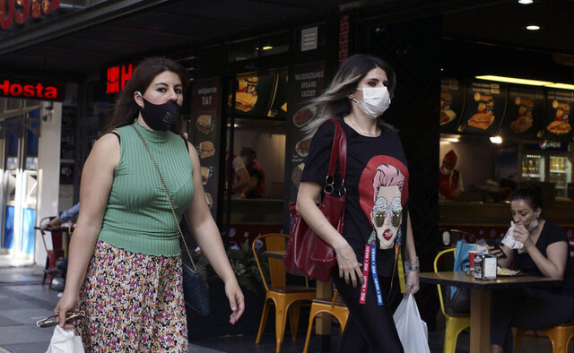Women wearing face masks to protect against the spread of coronavirus, walk in the city centre, in Ankara, Turkey, Wednesday, June 24, 2020. Turkish authorities have made the wearing of masks mandatory in three major cities to curb the spread of COVID-19 following an uptick in confirmed cases since the reopening of many businesses.(AP Photo/Burhan Ozbilici)
